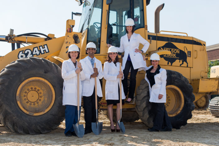 Editorial photograph of staff in from of an excavator machine, holding shovels for a breaking ground editorial piece by Kelly Ann Photography Dayton